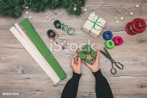 istock Packaging christmas present boxes . Top view of hands on white wood table with fir tree branches, decoration 859007918