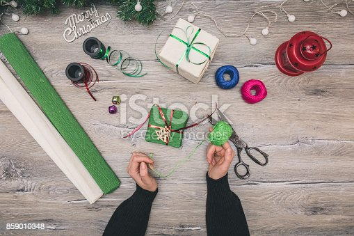 istock Packaging christmas present boxes . Top view of hands on white wood table with fir tree branches, decoration 859010348