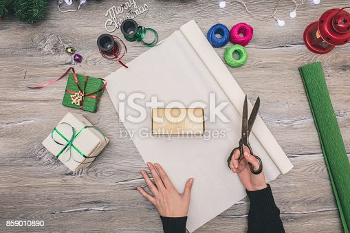 istock Packaging christmas present boxes . Top view of hands on white wood table with fir tree branches, decoration 859010890