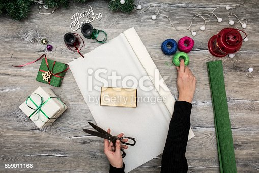 istock Packaging christmas present boxes . Top view of hands on white wood table with fir tree branches, decoration 859011166