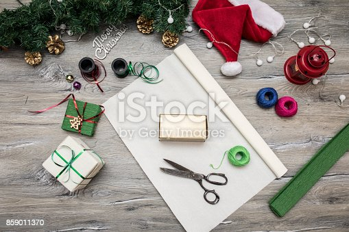 istock Packaging christmas present boxes . Top view of hands on white wood table with fir tree branches, decoration 859011370