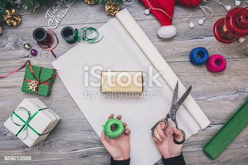 istock Packaging christmas present boxes . Top view of hands on white wood table with fir tree branches, decoration 859013588