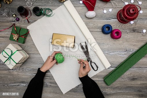 istock Packaging christmas present boxes . Top view of hands on white wood table with fir tree branches, decoration 859013816