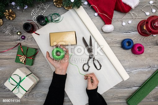 istock Packaging christmas present boxes . Top view of hands on white wood table with fir tree branches, decoration 859014134