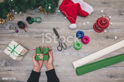 istock Packaging christmas present boxes . Top view of hands on white wood table with fir tree branches, decoration 859014778