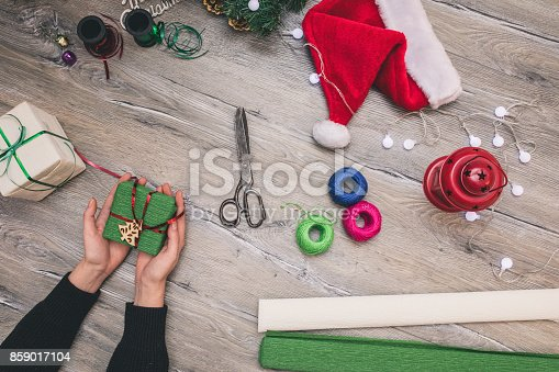 istock Packaging christmas present boxes . Top view of hands on white wood table with fir tree branches, decoration 859017104