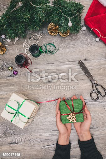 istock Packaging christmas present boxes . Top view of hands on white wood table with fir tree branches, decoration 859017448