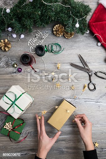 istock Packaging christmas present boxes . Top view of hands on white wood table with fir tree branches, decoration 859020670