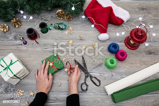 istock Packaging christmas present boxes . Top view of hands on white wood table with fir tree branches, decoration 859020982