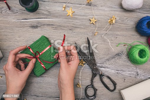 istock Packaging christmas present boxes . Top view of hands on white wood table with fir tree branches, decoration 859021392