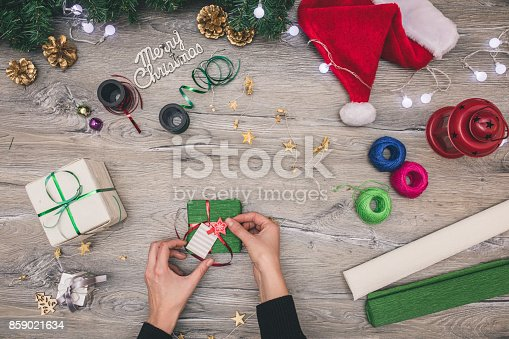 istock Packaging christmas present boxes . Top view of hands on white wood table with fir tree branches, decoration 859021634