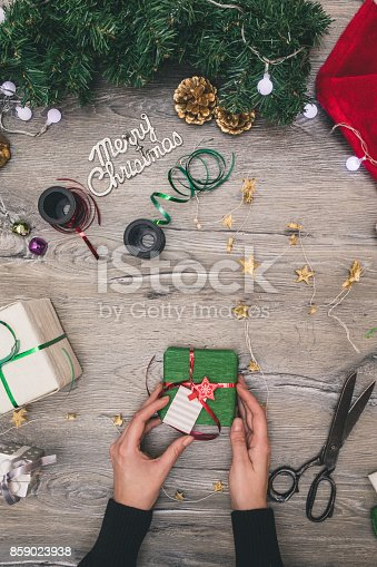 istock Packaging christmas present boxes . Top view of hands on white wood table with fir tree branches, decoration 859023938