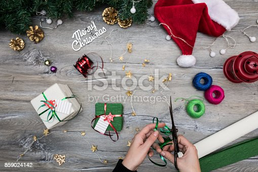 istock Packaging christmas present boxes . Top view of hands on white wood table with fir tree branches, decoration 859024142