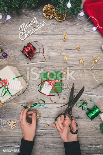 istock Packaging christmas present boxes . Top view of hands on white wood table with fir tree branches, decoration 859024556