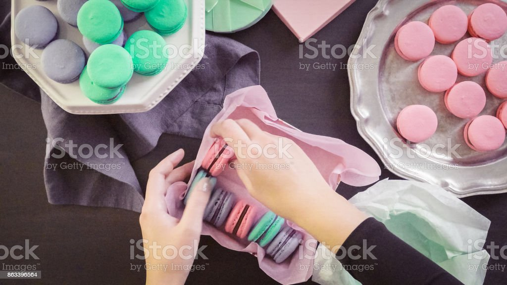 Packaging french macarons into gift boxes. stock photo