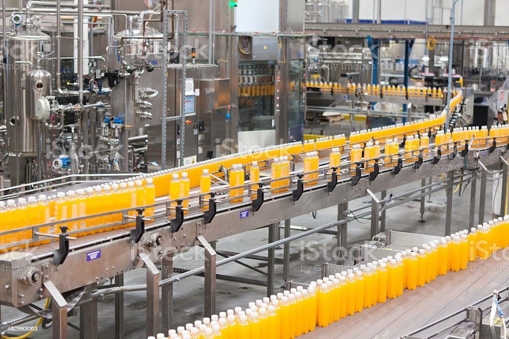 Packed bottles moving on conveyor belt in bottling industry stock photo