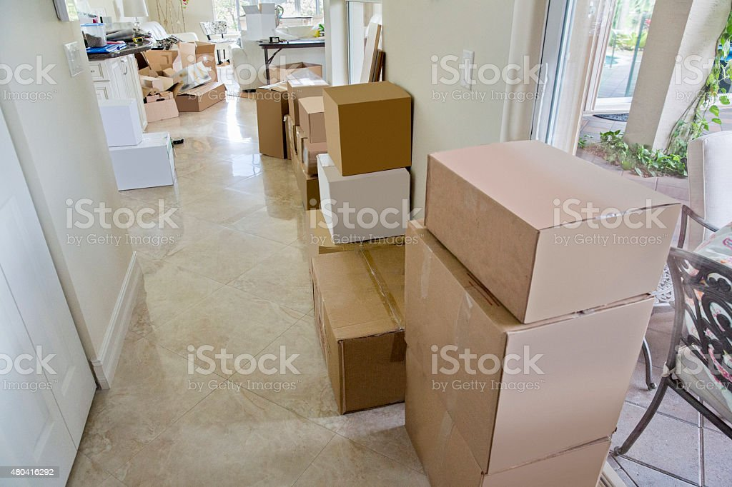 Packed boxes line hallway of home in preparation of moving stock photo