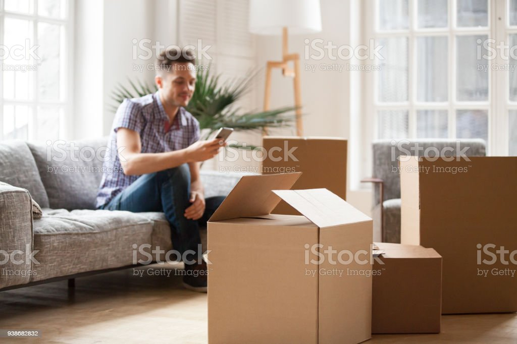 Packed cardboard boxes with man calling delivery service, moving concept stock photo