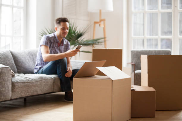 packed cardboard boxes with man calling delivery service, moving concept - tenant stock photos and pictures