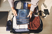 Close-up of man packing clothes in luggage for a trip