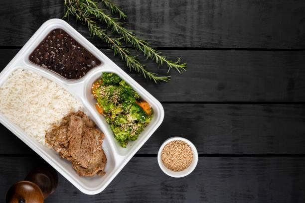 medhavd lunch - nötkött, broccoli och morot bakat med sesam, vitt ris och svarta bönor - lunchlåda bildbanksfoton och bilder