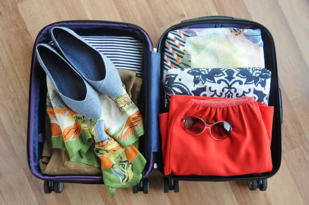 Packed Suitcase of Women's Clothing A packed suitcase with women's clothing and accessories. carry on luggage stock pictures, royalty-free photos & images
