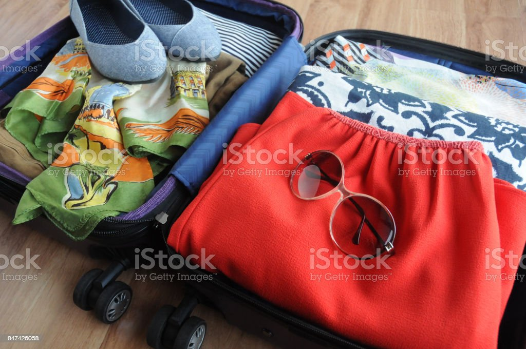 Packed Suitcase with Women's Clothing stock photo