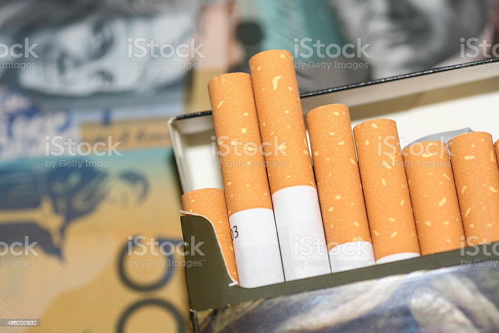 Open packet of expensive cigarettes in front of Australian fifty and...