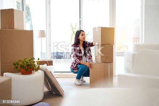 Full length shot of an attractive young woman stacking boxes while moving house