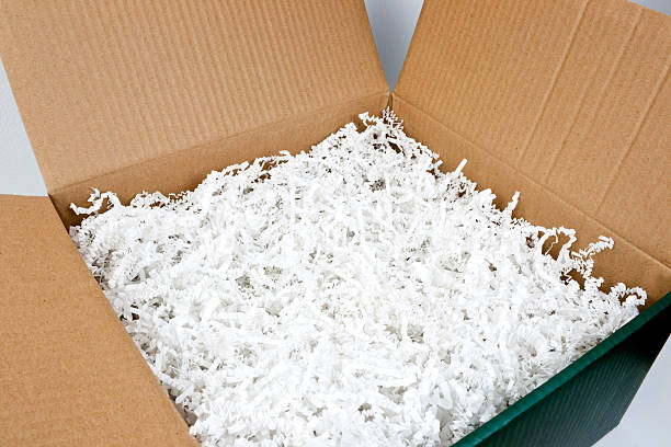 Packing box with shredded paper stock photo