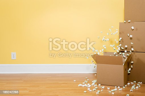 Packing Peanuts flying out of an open carboard box, with unopened boxes stacked against the wall inside of a home.