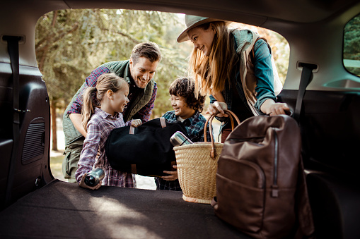 Close up of a young family packing up for a road trip
