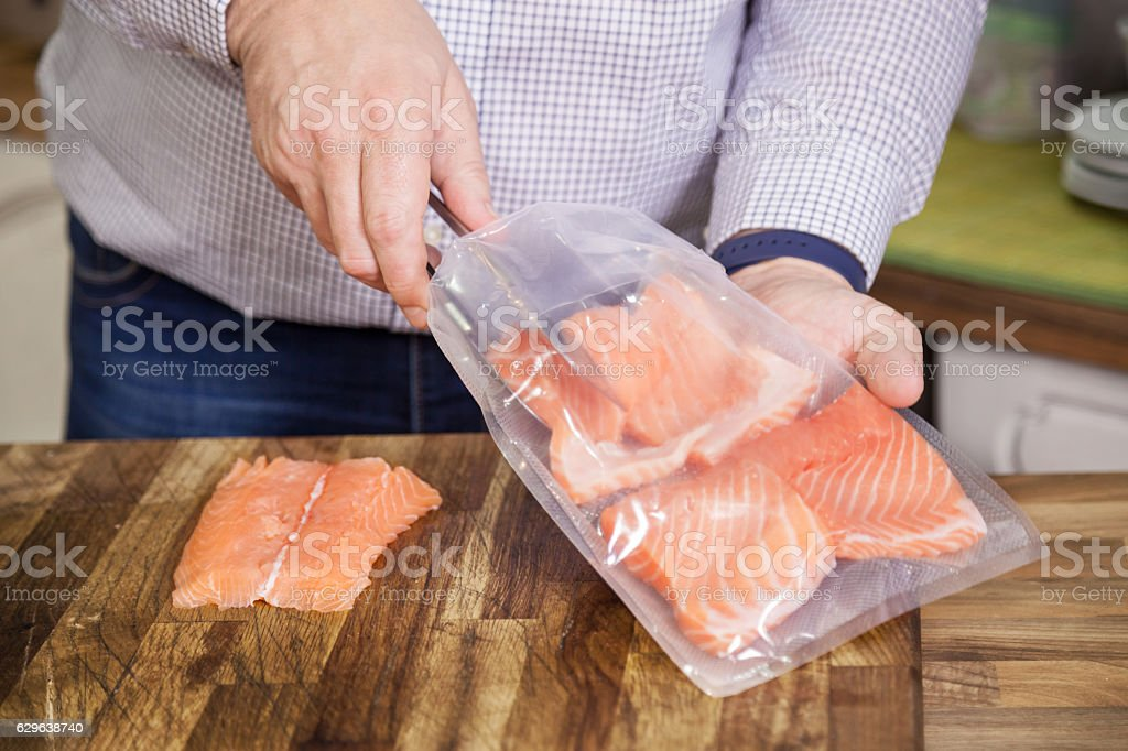 Packing salmon for sous vide. stock photo