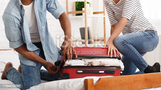 istock Packing suitcase. Couple trying to close valise 1154415762