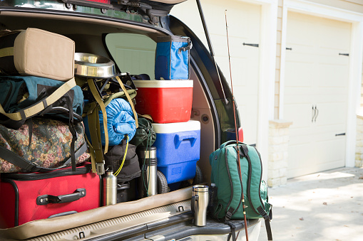 Vehicle fully packed for a hiking and camping trip. Dog bowl included.  Fishing rod and rifle included.