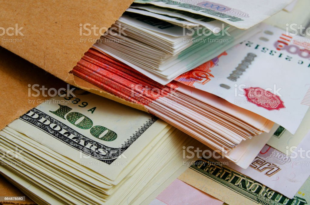Packs of dollars and rubles in a paper bag. stock photo