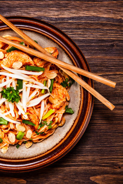 Pad thai - chicken meat with noodles and vegetables Pad thai - chicken meat with noodles and vegetables rice noodles stock pictures, royalty-free photos & images