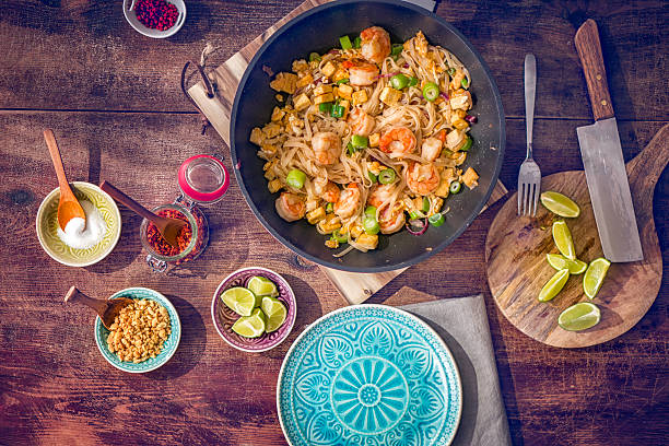 Pad Thai Noodles with Prawns Homemade pad thai noodle receipe with prawns, tofu, spring onions, ginger, peanuts and fried egg. asian food stock pictures, royalty-free photos & images