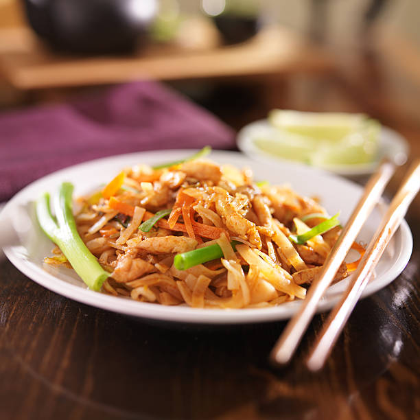 pad thai with chicken dish close up photo of a plate pad thai with chicken rice noodles stock pictures, royalty-free photos & images