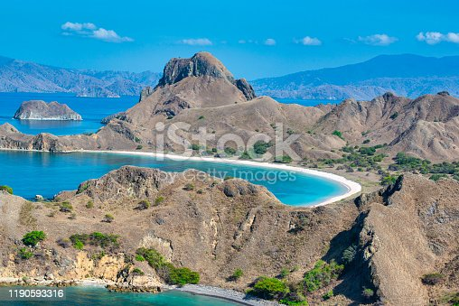 Aerial shot of the mountains and bays of Padar island (Pulau Padar) in the Komodo National Park, Lesser Sunda Islands, Indonesia. In the background the island Komodo is visible, this is the home of the Komodo Dragon (Varanus komodoensis), the largest living species of lizard, growing to a maximum length of 3 meters.