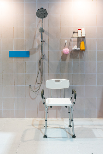 istock Padded shower chair with arms and back in bathroom with bright tile wall and floor. 841692252
