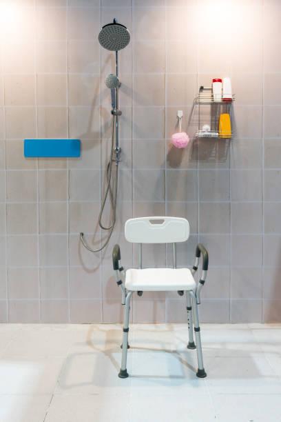 Cadeira de banho com os braços e volta na casa de banho com azulejo brilhante parede e chão de acolchoado. - foto de acervo