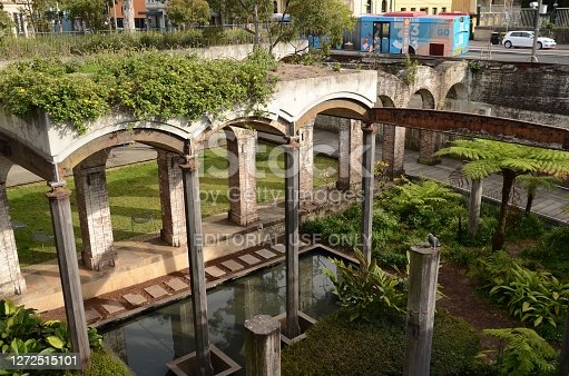Paddington Reservoir Gardens with old stone arches reflected in pool. Oxford Street in the background with bus