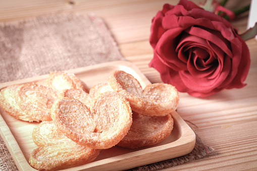 Paddle a butterfly, heart shaped patty crispy with sugar in a wooden plate , The concept of Valentine's Day.