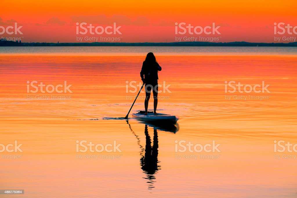 Paddle Board in the sunset with silhouette girl stock photo