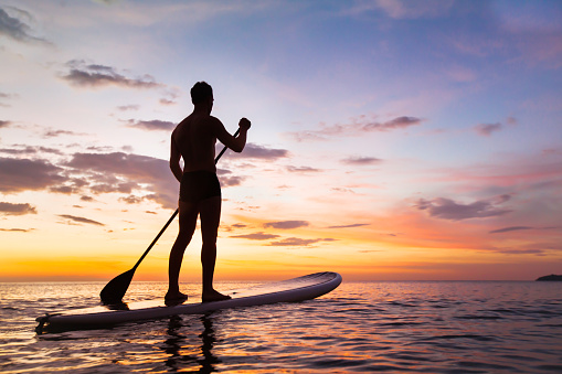 SUP paddle board silhouette at sunset