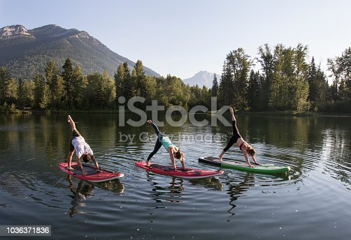 Three people practicing yoga on a paddle board with mountains in the background.