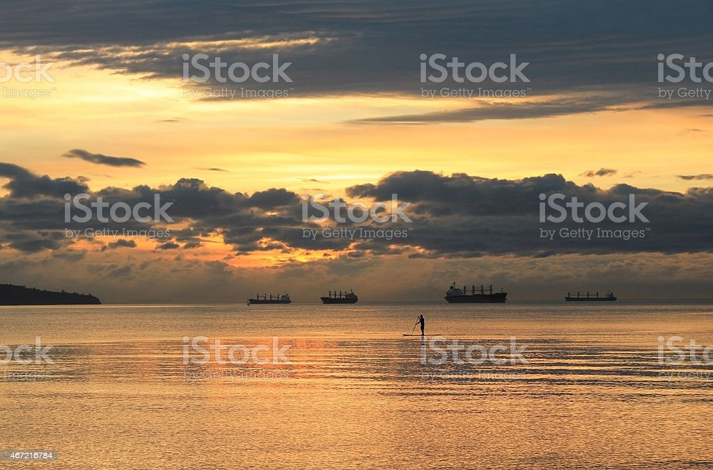 Paddle boarder during sunset in Vancouver Bay stock photo