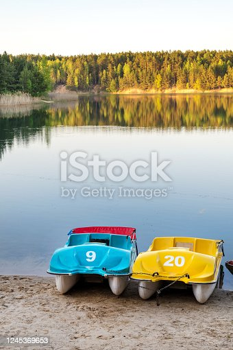 Colorful paddle boats on sandy beach by one of the Blue Lakes, Chernigiv region, Ukraine