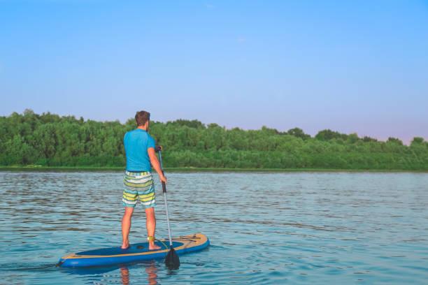 stand-up-paddle - stehpaddeln stock-fotos und bilder